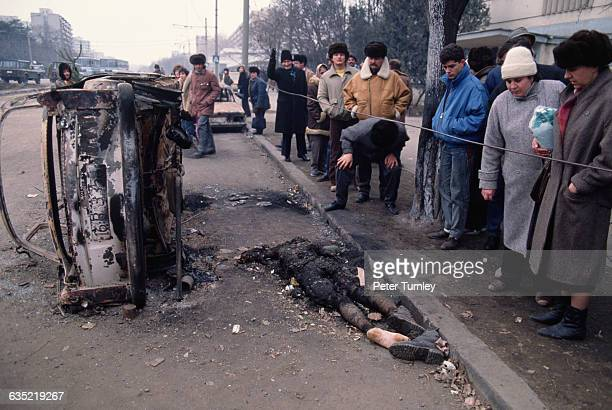 Residents of Bucharest file past the burned remains of a Securitate officer and his car on a city street