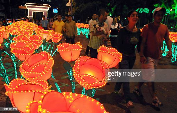 Residents of Cali stroll a park illuminated with Christmas lights on December 2 2008 AFP PHOTO/Luis ROBAYO