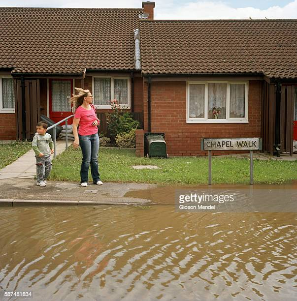 Residents of Catcliffe Village survey one of the flooded streets of their village This was one of the communities flooded when a freak tropical storm...
