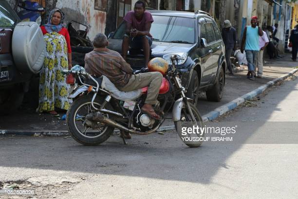 Residents of Comoros Island Anjouan main city Mutsamudu stand by a crossroad in the neighbourhood of Chitangani on October 19 2018 in Anjouan Comoros...