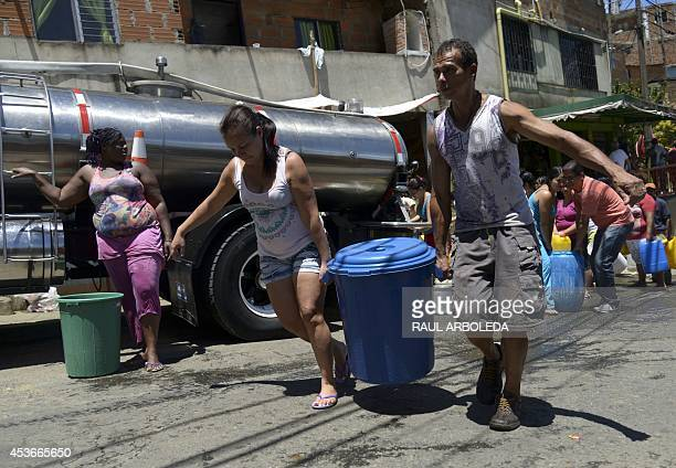 Residents of Comuna 8 shantytown carry a container full of water they collected from a tanker in the slum on the outskirts of Medellin Antioquia...