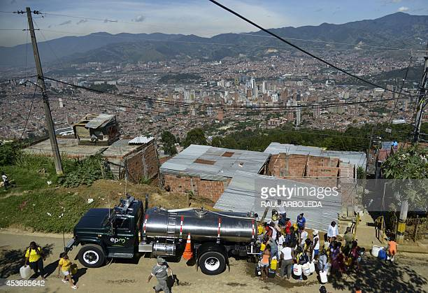 Residents of Comuna 8 shantytown collect water from a tanker in the slum on the outskirts of Medellin Antioquia department Colombia on August 15 2014...