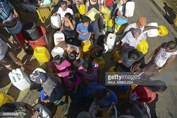 Residents of Comuna 8 shantytown wait to collect water from a tanker in the slum on the outskirts of Medellin Antioquia department Colombia on August...