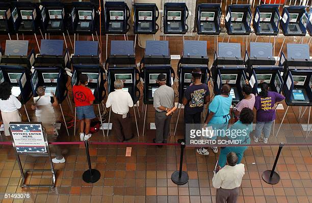 Residents of Dade County work electronic voting machines at a local voting station in Miami 18 October 2004 The electronic voting machines are new in...