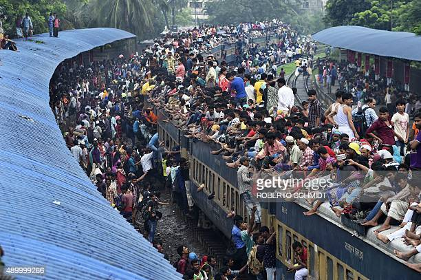 Residents of Dhaka scramble to reach the roof of an overcrowded train at a train station in Dhaka on September 25 2015 Muslims across the world...