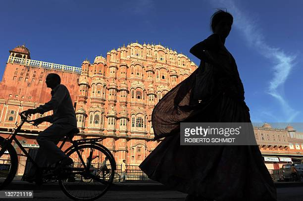 Residents of file past the Hawa Mahal 'Palace of Winds' in the old walled city of Jaipur on November 14 2011 The iconic building was designed to...