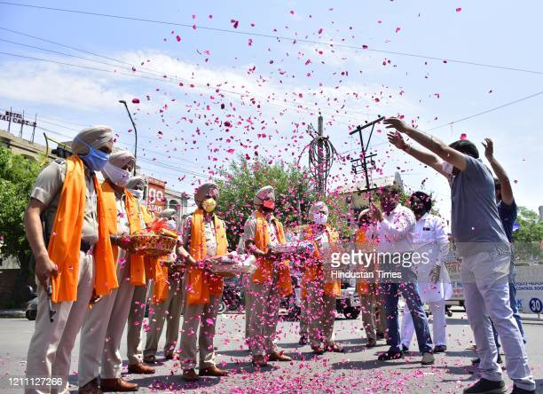 Residents of Green avenue shower flower petals on Punjab Police personnel for their service during the lockdown to check the spread of coronavirus,...