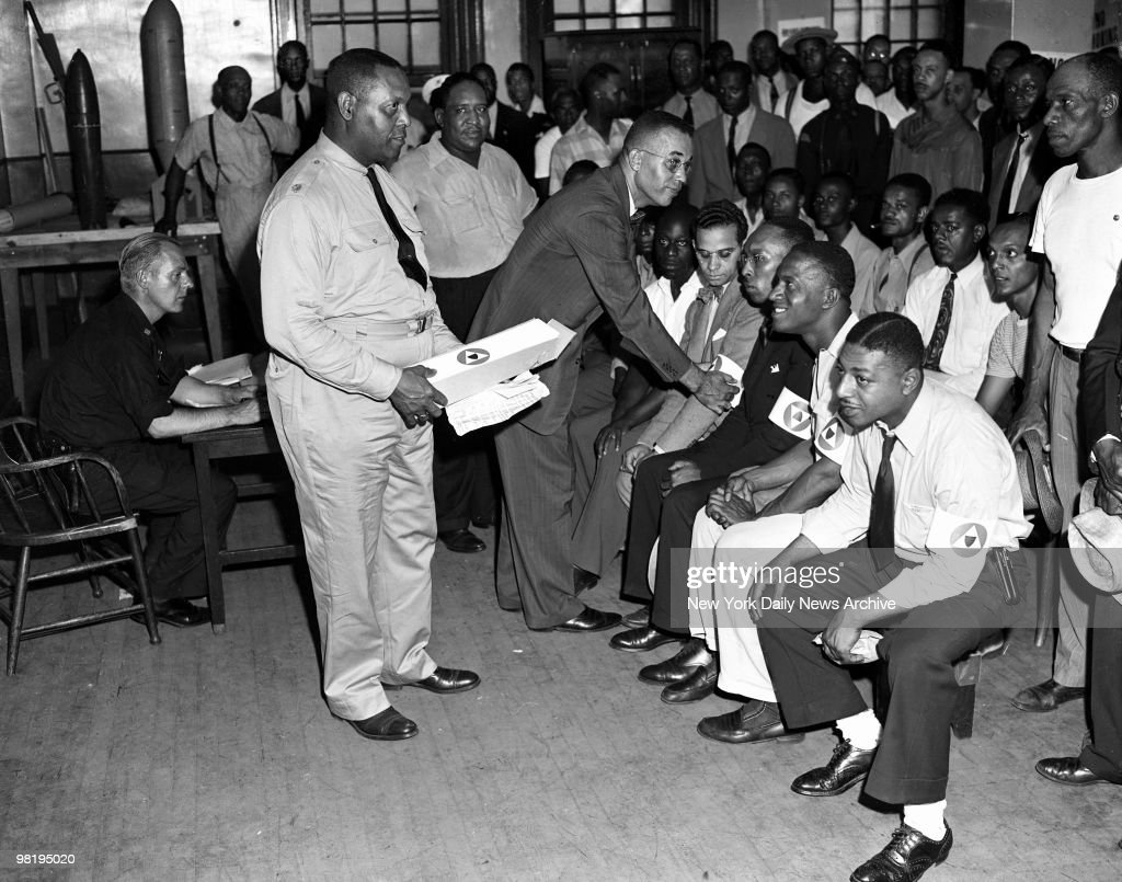 Residents of Harlem were quick to volunteer their services to help restore order to the district on August 2, 1943 in Harlem, New York. Major Samuel J. Battle (in uniform) and Edward S. Lewis, executive secretary of the N.Y. Urban League, pin auxiliary arm bands on the volunteers, who will patrol the streets. Mayor LaGuardia emphasized that disturbance was not a race riot.