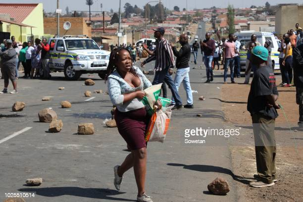 Residents of Jabavu loot shops allegedly owned by foreign nationals on August 29 2018 in Soweto South Africa Violence and riots erupted in Soweto...