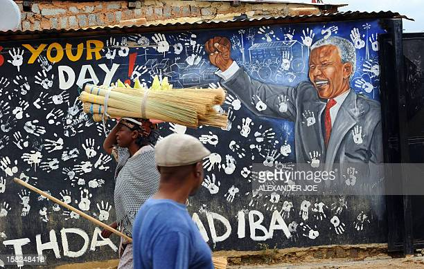 Residents of Johannesburg's Alexandra Township walk on December 12 2012 past a portrait of former South African President Nelson Mandela painted on a...