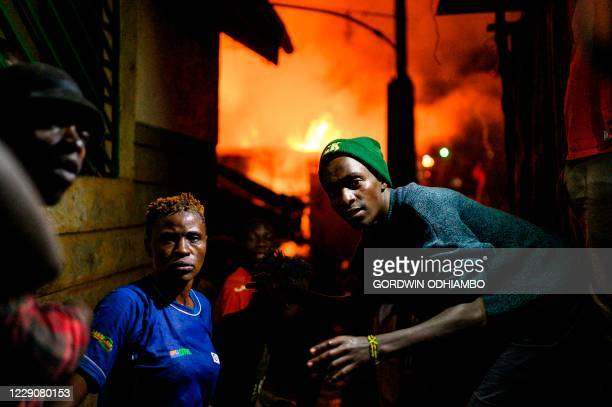 Residents of Kibera form a human-chain as they pass water to extinguish a fire that gutted shantees in the Maranatha area of the sprawling slum that...