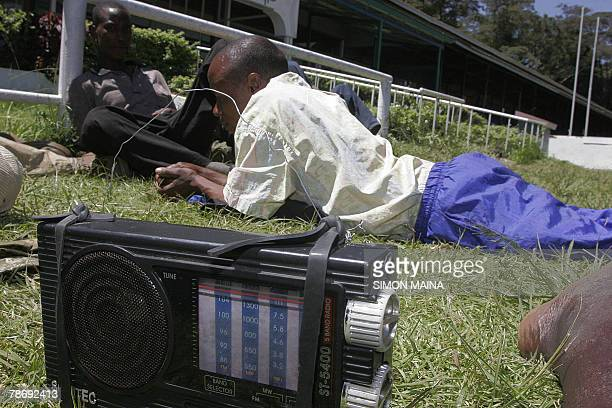 Residents of Kibera listening to the radio in their new shelter at the Jamhuri grounds in Nairobi 02 January 2008 where they have spend three days...