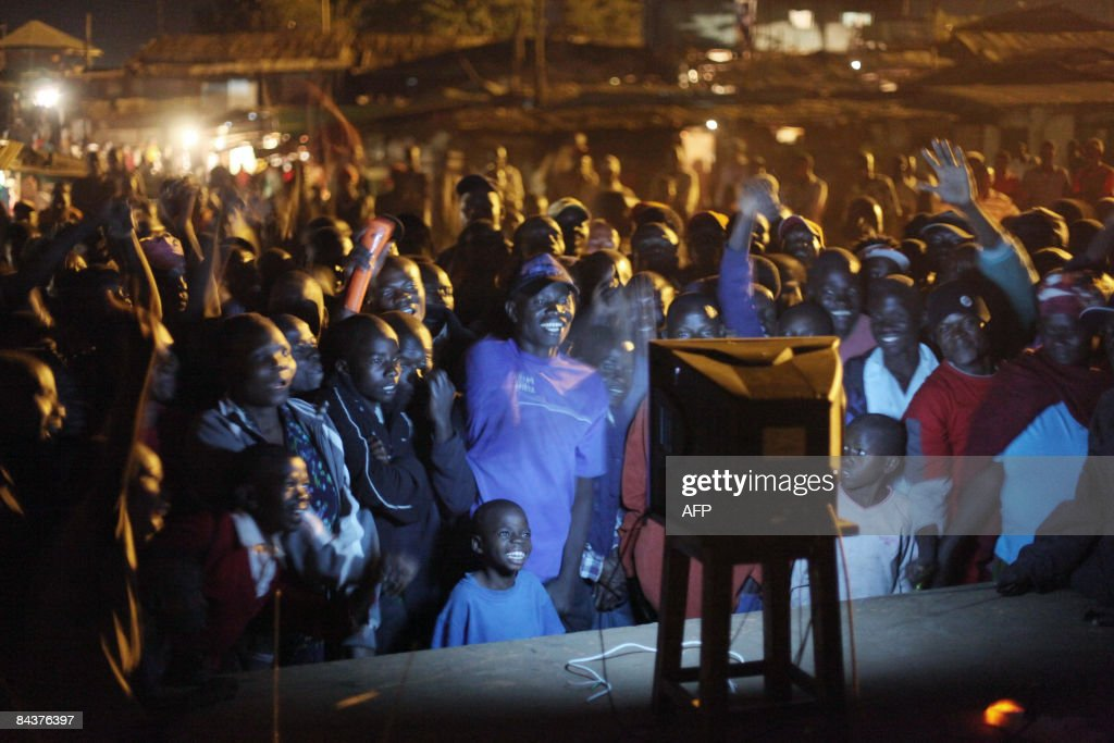 Residents of Kibera, one of Nairobi's poorer quarters gather around a TV set on January 20, 2009 as they watch the inauguration ceremony of Barrack Obama as he became the 44th President of the United States. Obama took the oath of office to become the first black president in US history, proclaiming America had chosen 'hope over fear' and must unite in a 'new era of responsibility' to triumph over its multiple crises. AFP PHOTO / Yasuyoshi CHIBA