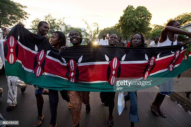 Residents of Kisumu celebrate with the Kenyan flag on the streets of Kisumu after hearing news that Kenya's opposition leader Raila Odinga had signed...