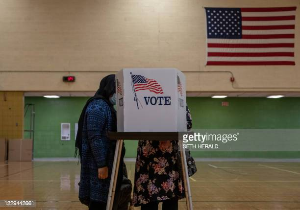 Residents of Lansing, Michigan, cast their votes November 3, 2020. - Americans were voting on Tuesday under the shadow of a surging coronavirus...