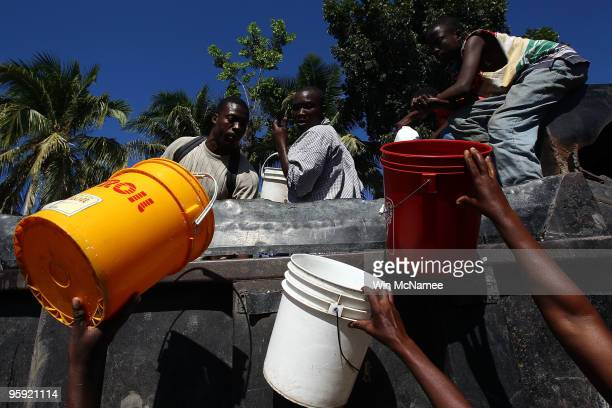 Residents of Leogane reach out during a distribution of water by city workers January 21 2010 in Leogane Haiti Aid has been slow in reaching outlying...