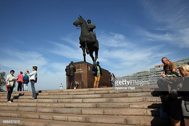 Residents of Lugansk search for a cell phone reception under a Soviet area statue on September 14 2014 in Lugansk Ukraine Lugansk a separatist held...