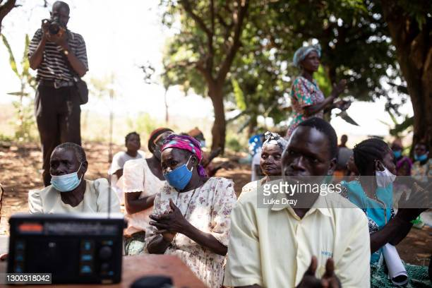 Residents of Lukodi clap as a guilty verdict is returned as they listen to the the court case via a radio on February 04, 2021 in Gulu, Uganda. On...