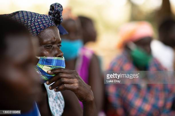 Residents of Lukodi react as they listen to the the court case via a radio on February 04, 2021 in Gulu, Uganda. On May 19 2004, more than sixty...