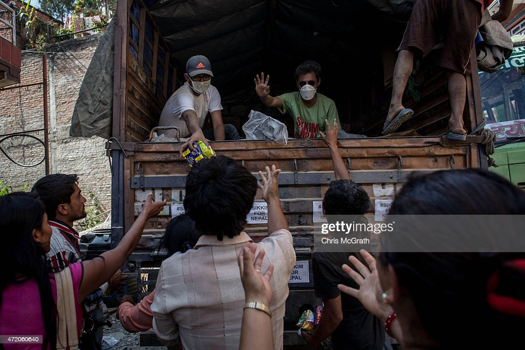 Residents of Melamchi chase after a truck giving out noodles and water on May 3, 2015 in Nepal. A major 7.9 earthquake hit Kathmandu mid-day on Saturday, and was followed by multiple aftershocks that triggered avalanches on Mt. Everest that buried mountain climbers in their base camps. Many houses, buildings and temples in the capital were destroyed during the earthquake, leaving over 6000 dead and many more trapped under the debris as emergency rescue workers attempt to clear debris and find survivors. Regular aftershocks have hampered recovery missions as locals, officials and aid workers attempt to recover bodies from the rubble.