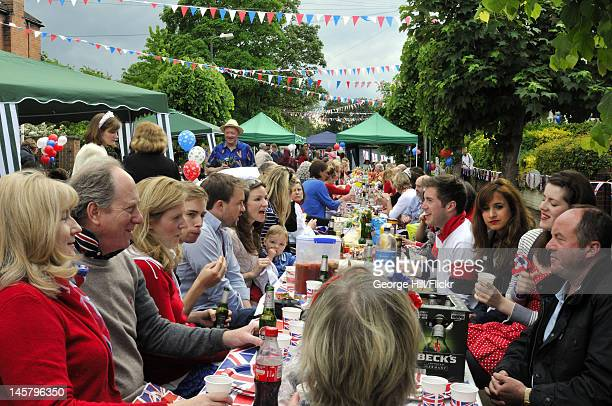 Residents of Melbourne Road, Wimbledon, South West London are seated at a long union-jack bedecked table enjoying food, drink and conversation during...