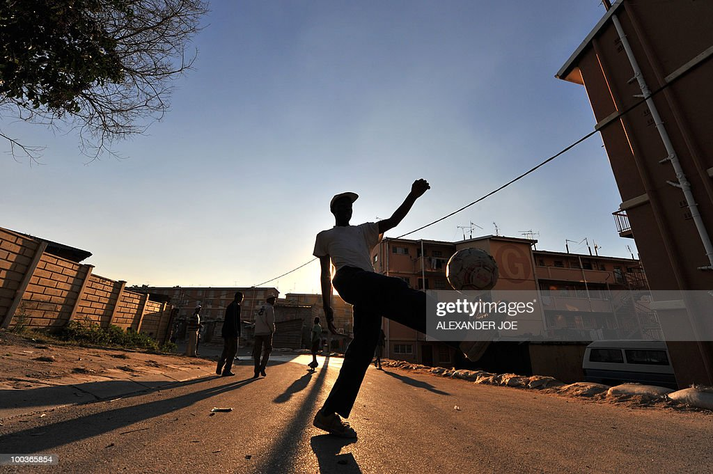Residents of north Johannesburg's Alexandra township play football in the street on May 23, 2010.