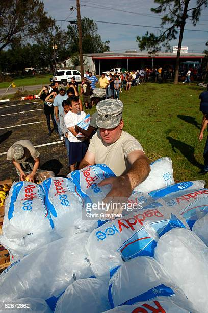Residents of Pasadena, TX receive ice, water, and food from members of the Texas National Guard after being affected by Hurricane Ike September 15,...