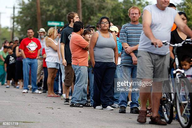 Residents of Pasadena TX wait in line to receive ice water and food from members of the Texas National Guard after being affected by Hurricane Ike...