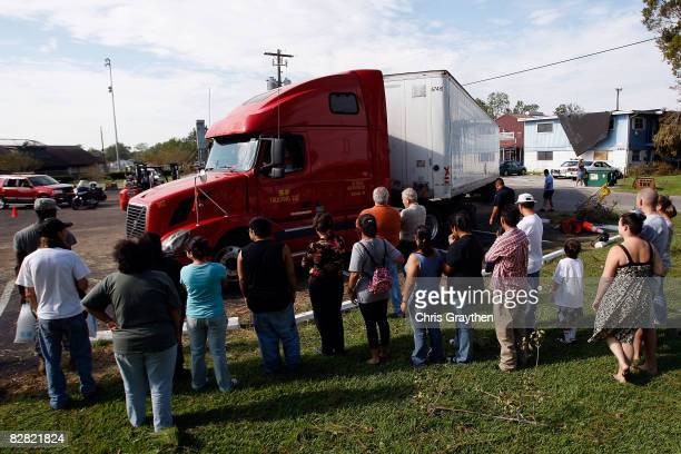Residents of Pasadena, TX watch as an truck delivering ice, water, and food arrives to be distributed by members of the Texas National Guard after...