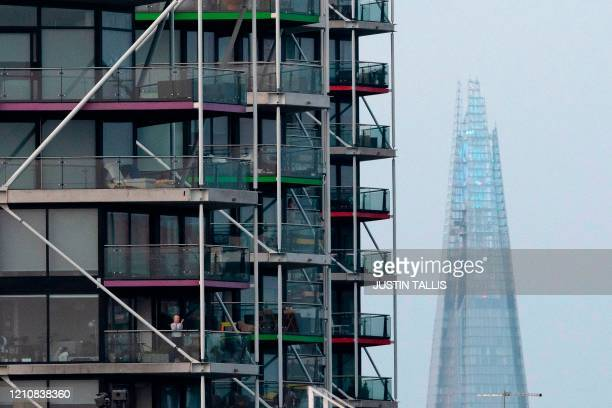 """Residents of Riverlight Quay apartment buildings stand on their balconies as they take part in a national """"clap for careers"""" to show thanks for the..."""