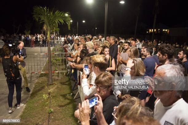 Residents of SaintBarthélemy gather to pay a last tribute to French music icon Johnny Hallyday before his burial during the public wake at the Saint...