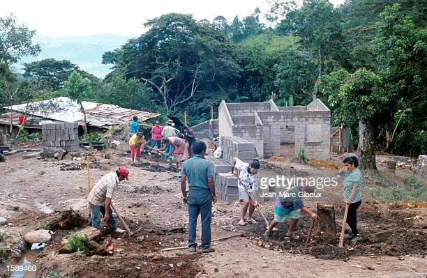 Residents of San Juancito Honduras clear land for 52 new homes October 1999 to be built in their town by the Kaputzihil Rotary Club of Tegucigalpa...