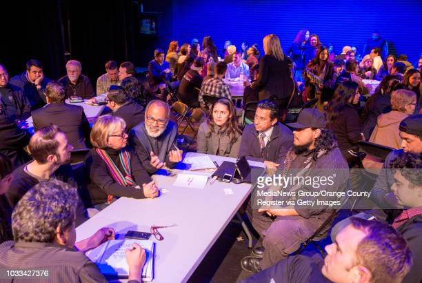 Residents of Santa Ana and people involved in the arts sit in groups on the stage at Santa Ana College's Phillips hall to meet and discuss the Santa...