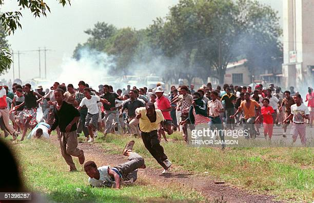Residents of Sharpeville flee 26 March 1990 after police fired teargas to disperse demonstrators who had formed an illegal march to protest against...