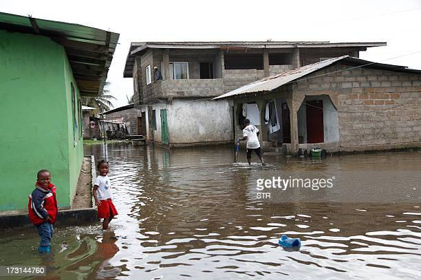 Residents of SK Doe slum community stand in a flooded street after heavy rainfalls in Monrovia on July 8 2013 AFP PHOTO / STR