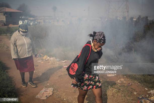 Residents of Snake Park in Soweto walk through burning grass at the site of a demonstration against the electricity cuts on May 13 2020