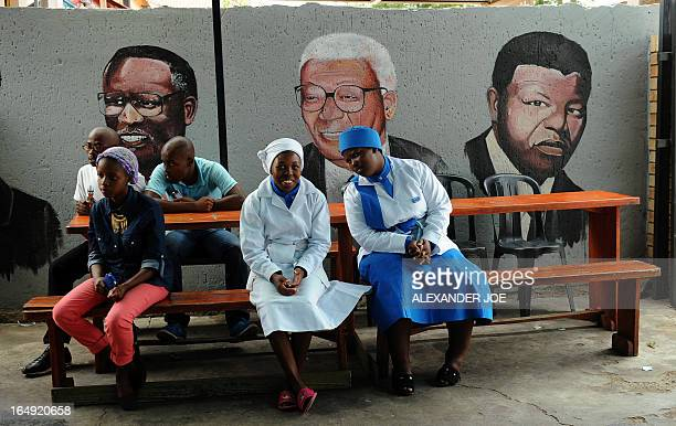Residents of Soweto wait for their takeaway food at a restaurant in Soweto on March 29 2013 in front of a wall bearing painted portraits of former...