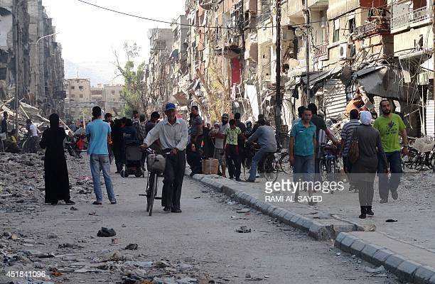 Residents of Syria's Yarmuk Palestinian refugee camp south of Damascus gather to collect aid food on July 7 2014 Forces loyal to President Bashar...