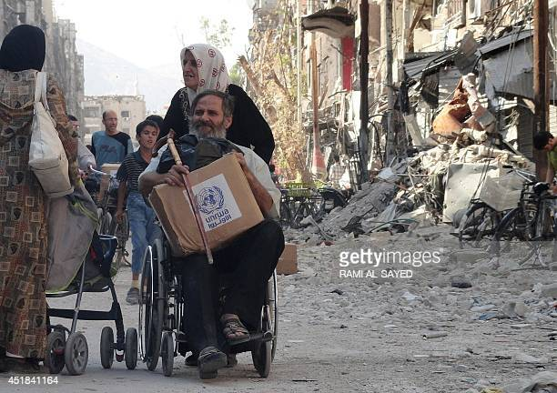 Residents of Syria's Yarmuk Palestinian refugee camp south of Damascus collect aid food on July 7 2014 Forces loyal to President Bashar alAssad have...
