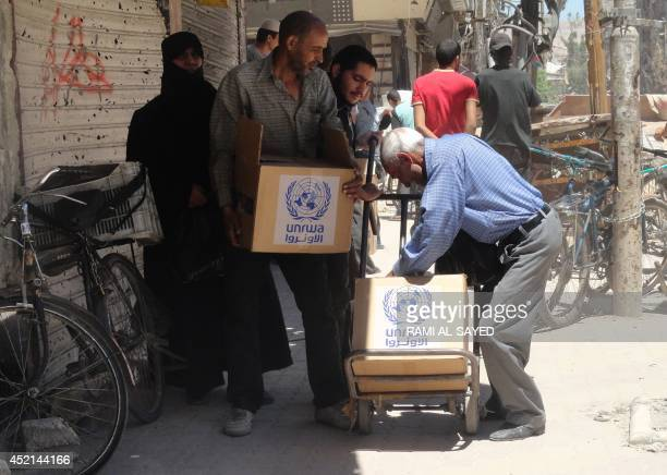 Residents of Syria's Yarmuk Palestinian refugee camp south of Damascus gather to collect aid food on July 14 2014 Forces loyal to President Bashar...