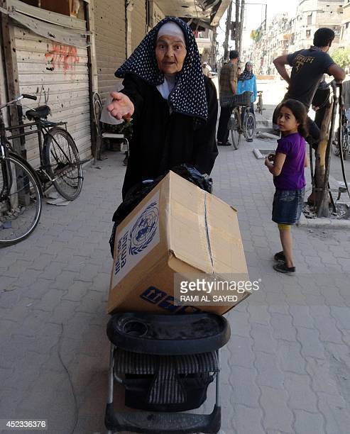 A residents of Syria's Yarmuk Palestinian refugee camp south of Damascus uses a pushchair to carry a box of goods distributed by the United Nations...