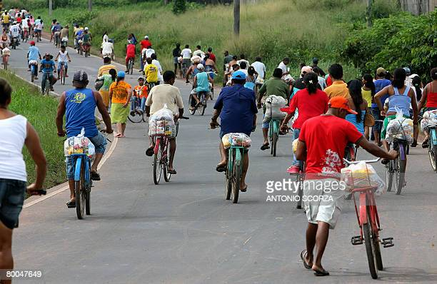 Residents of Tailandia on bike leave the farm of Tailandia's mayor after receiving a basket of basic food on February 28 2008 in Tailandia in the...