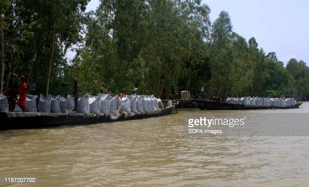 Residents of Tangail work to repair the embankment designed to protect their land from flooding Over million people have been affected by floods...