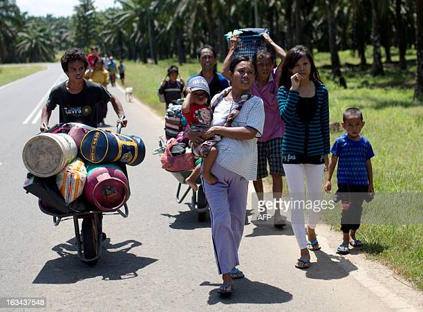 Residents of Tanjung Labian leave their village near where Filipino gunmen were locked down in a stand off in the surrounding villages of Tanduo in...