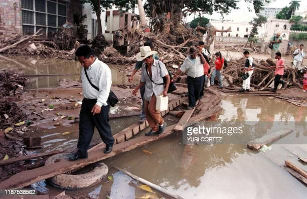 Residents of Tegucigalpa use planks to cross standing water left after floods by Hurricane Mitch in the Honduran capital 11 November An estimated 24...