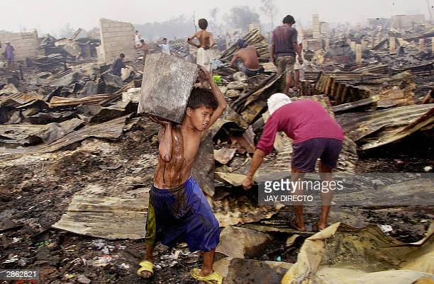 Residents of the Baseco shanty town in Manila's Tondo district sift through the rubble for reusable materials after a blaze razed the area 12 January...