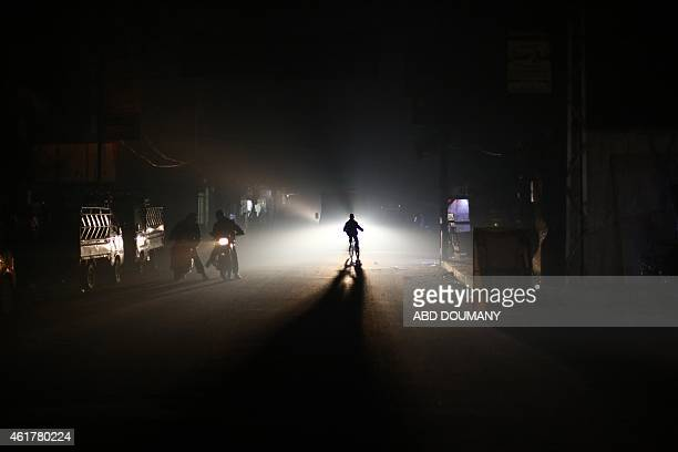 Residents of the besieged rebel town of Douma 13 kilometres northeast of Damascus ride through the street at night during an electricity shortage on...