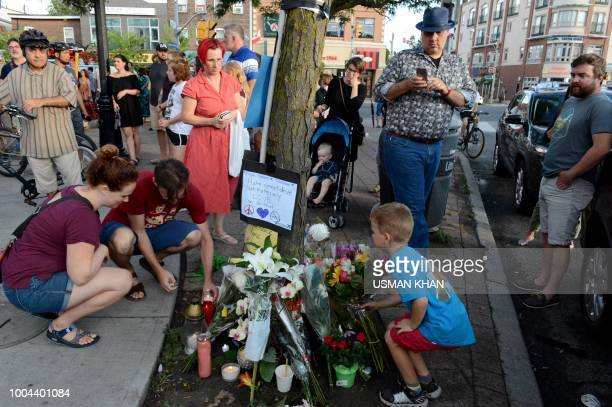 Residents of the Danforth area leave flowers and light candles for the victims at the scene of last night shooting in Toronto Ontario on July 23 2018...