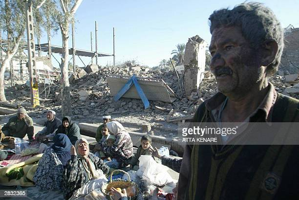 Residents of the devastated southeastern Iranian city of Bam 26 December 2003 huddle among the rubble after an earthquake measuring 63 on the...