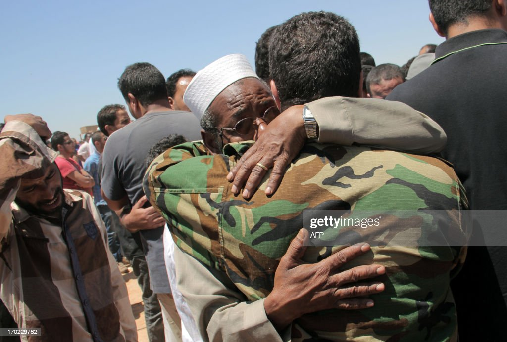 Residents of the eastern Libyan city of Benghazi mourn on June 9, 2013 as they bury the bodies of the demonstrators that were killed during clashes between former rebels and anti-militia protestors the previous day. The fighting erupted after dozens of demonstrators, some of them armed, tried to dislodge the powerful 'Shield of Libya' brigade from its barracks, an AFP correspondent at the scene said.